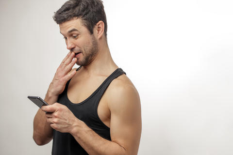 curious young man looking at his mobile phone and closing his mouth フォト