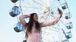 A young girl with long hair in a long dress makes selfie using a smartphone Footage