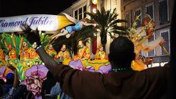 People on a Mardi Gras Float Toss Beads to People Below 4120 Footage
