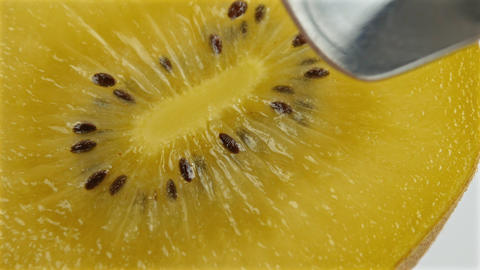 4k macro shot , juicy kiwifruit with seeds as spoon digs in to scoop out brown Footage