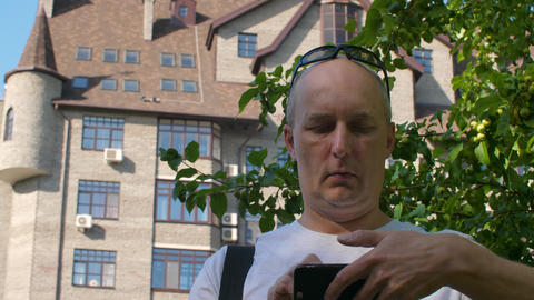 Bald man editing video on smartphone in city with tree and building Footage