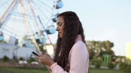 A young girl walks by the ferris wheel and uses a smartphone. 4K 영상물