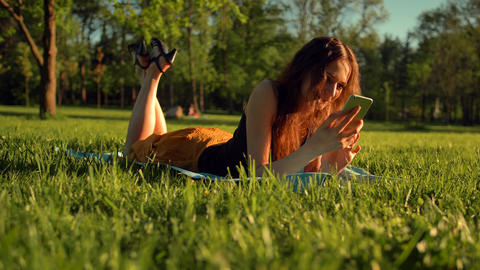Happy female types sms or chat, sitting in park on grass. Woman chatting in Live Action