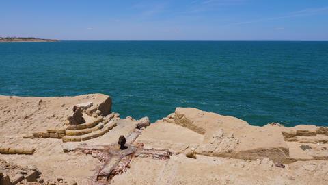 Old rusty bitt knecht on rocky coast with sea on horizon Footage