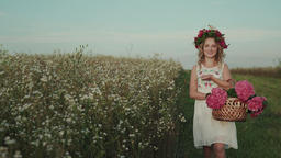 Beauty woman with a flowers and a wreath on her head walks in the field Footage