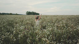 Beauty girl with flower wreath on head running cross the flower field at sunset Live Action