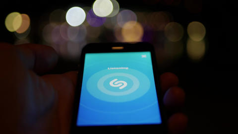 Using music discovery identification software application Shazam on a smartphone Live Action