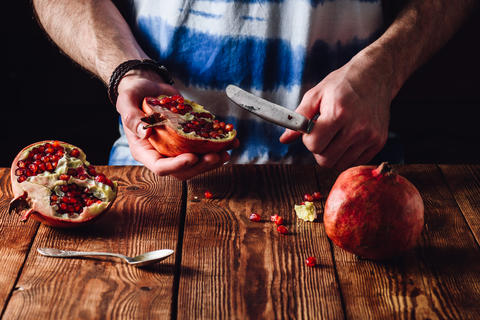 Pomegranate and Knife in Human Hands Fotografía