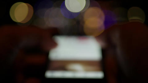Using smartphone at night with city lights in background - blurry bokeh concept Footage