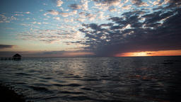 Time lapse of Sun rising over the water on a beach with the horizon and clouds Footage