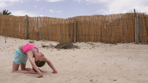 Young acrobatic child doing somersault on sandy beach Footage