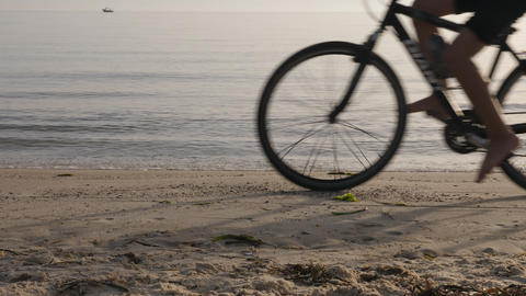 Person riding bicycle and traveling on beach near sea , cropped view GIF