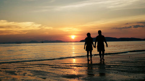 Couple kissing and walking on the beach at sunset Footage