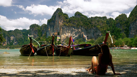 Girl relaxing near long tail boats on a tropical beach, Live Action