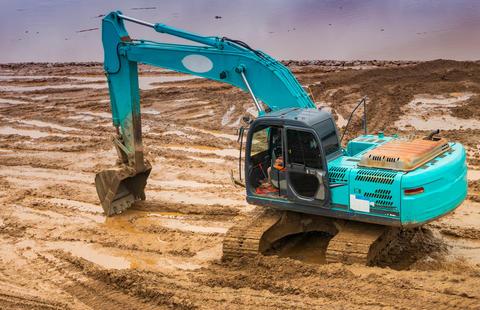 Backhoe digging the ground to build a riverside river road Fotografía