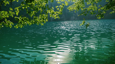 Morning sun reflection on a clear blue lake Footage