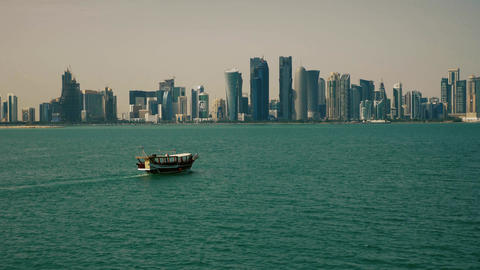 Traditional fishing boat passing near skyscrapers in doha qatar Live Action
