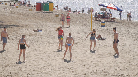 A group of young people playing beach volleybal ビデオ
