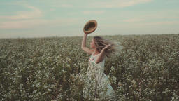 Girl with a hat in her hand walks in a field with field flowers Footage