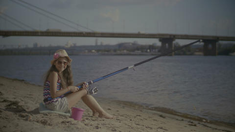 Portrait of smiling girl sitting at bank and fishing Footage