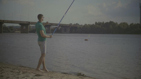 Joyful millennial man catching fish on river bank Footage