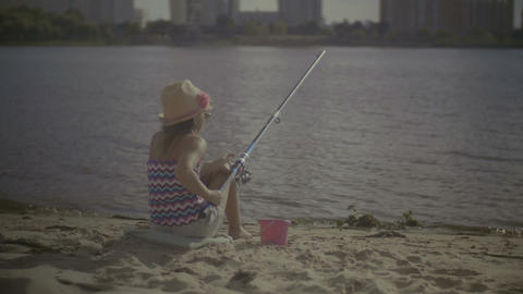 Beautiful little girl fishing with spinning rod Footage