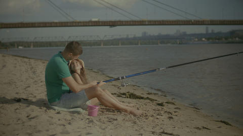 Lovely girl and father relaxing on river bank Footage