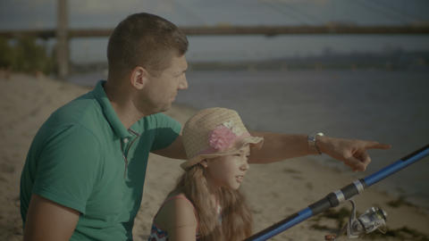 Joyful family catching a fish from shore on river Footage