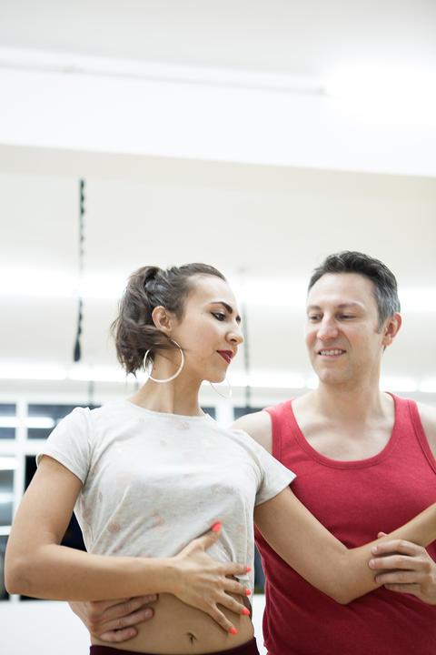Beautiful couple dancing on latino rhythm in big studio hall フォト