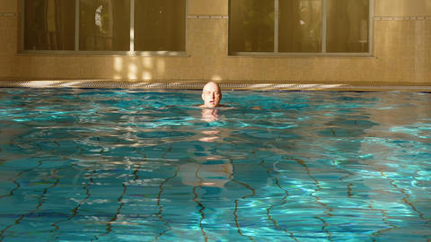 Man swimming breaststroke in indoor pool, front view. Sportive lifestyle Footage