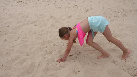 Young acrobatic girl doing gymnastic bridge and somersaults on sand Footage