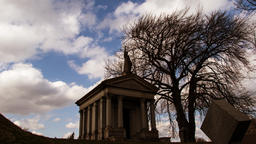 Time lapse of Roman Style tombstone mausoleum with a bare tree in silhouette and Footage