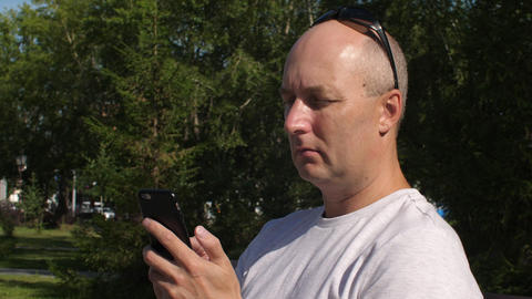 Adult man using mobile phone for chatting in social networks outdoor GIF