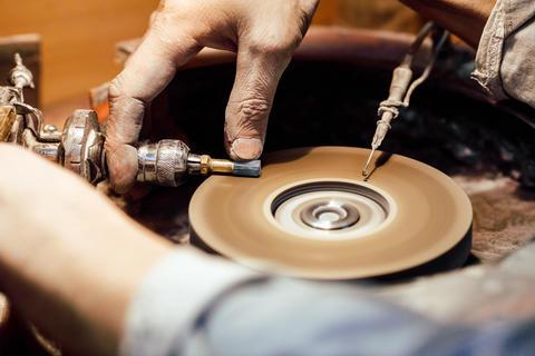 Jeweller polishing a stone blue cubic zirconia フォト