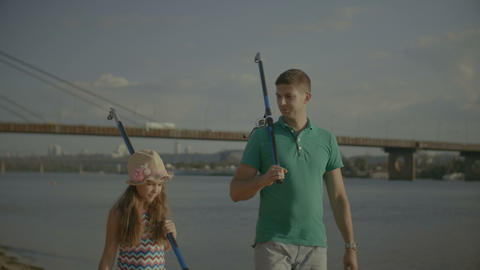 Father with cute daughter carrying fishing rods Footage