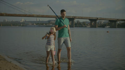 Carefree family with fishing rods walking in water Footage