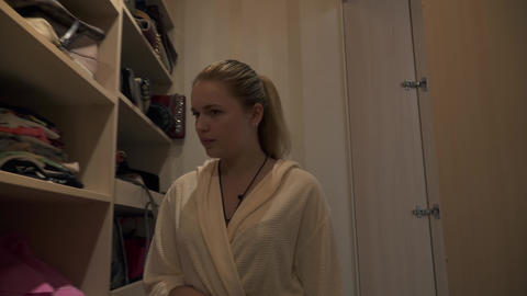 Young blonde entres into the dressing room and takes a dress off the shelf Footage