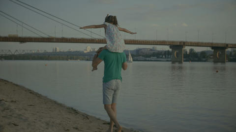 Father playing with his daughter carrying her on shoulders Footage