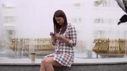 A girl sits near a fountain in the park and uses a smartphone. slow motion 영상물