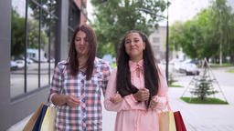 Two young girls in dresses go after shopping and carry shopping in packages ビデオ