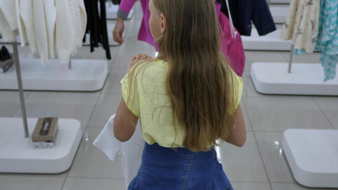 Blonde girl carrying clothes to fitting room in boutique Footage