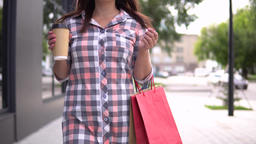 The girl goes after shopping with bags in her hands drinking coffee. 4K Footage