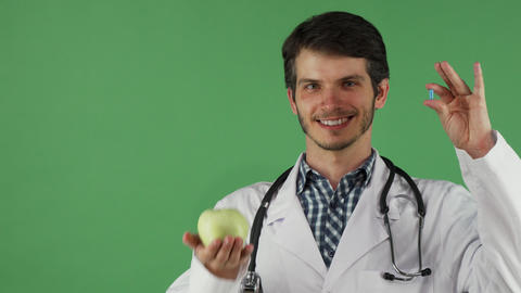 Cheerful male doctor holding vitamin pill and an apple ビデオ