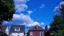 Time lapse of clouds forming in the sky over the roofs of houses in the summer Footage