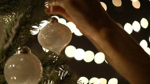Female decorating Christmas ball on tree with bokeh lights Footage
