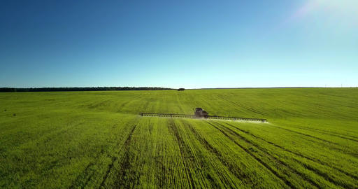 drone moves to trailed sprayer silhouette under sunlight Live Action