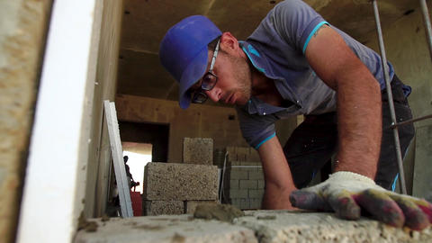 Worker builds a concrete wall with a spatula puts the solution on the concrete Live Action