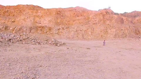 Lonely young woman walking barefoot on the sand in the background of the Footage