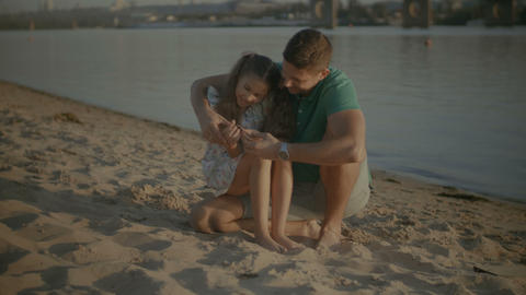 Child and father looking for shells in the sand on beach Footage