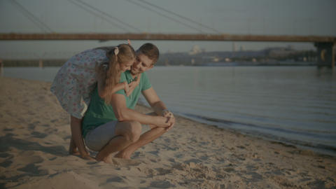 Smiling little girl embracing father on beach Footage